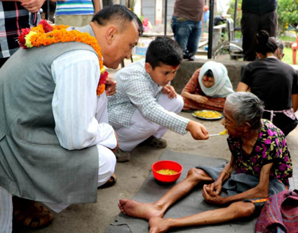 Sanat Kumar Basnet (left) watches his son Bardan celebrate his 11th birthday by feeding an elderly woman at the social welfare center at the Pashupatinath temple in Kathmandu, Nepal, July 4. (CNS photo/Anto Akkara)