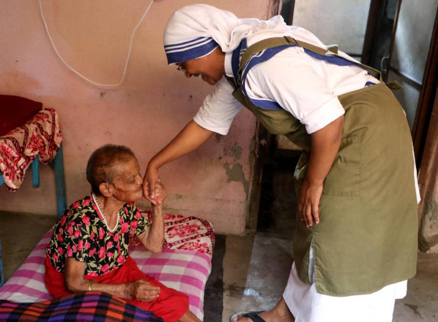 An elderly woman kisses the hand of Sister Marica of the Missionaries of Charity at a home for the elderly in the Pashupatinath temple in Kathmandu, Nepal, July 4.  (CNS photo/Anto Akkara)