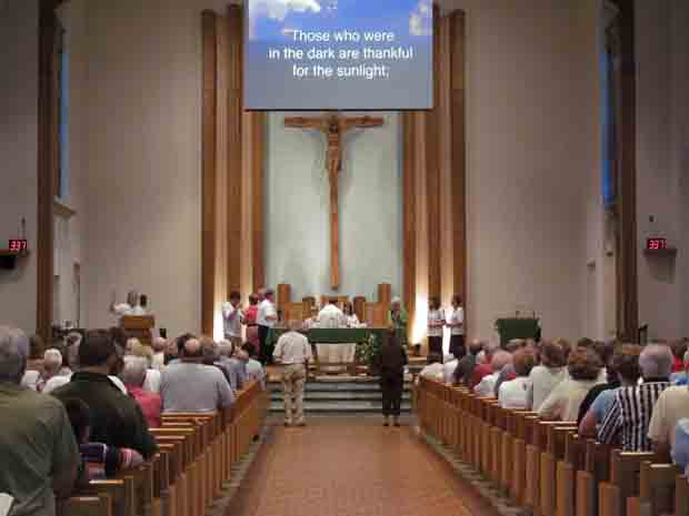 Saturday evening Mass is celebrated at the Waldo worship site of St. Francis of Assisi Parish in Manitowoc, Wisconsin, June 23, 2012. The worship site is one of three former parish churches now used by the single city-wide St. Francis. Prayers and song lyrics are projected on the screen. (CNS photo/Patricia Zapor)