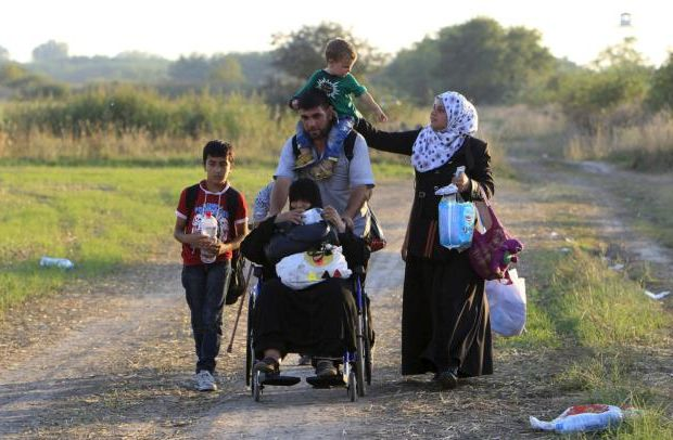 Syrian migrants travel along a road after crossing into Hungary from the border with Serbia near Roszke, Hungary, Aug. 29. About 100,000 migrants, many of them from Syria and other conflict zones in the Middle East, have taken the Balkan route into Europe this year, heading via Serbia for Hungary and Europe's Schengen area of passport-free travel. (CNS photo/Bernadett Szabo, Reuters)