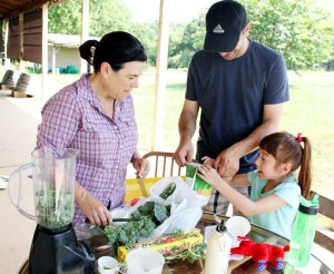 Joanne Rosenbaum, education coordinator, shows Louis Pavone and his daughter Sophia how to make healthy smoothies from things the pick at the farm.