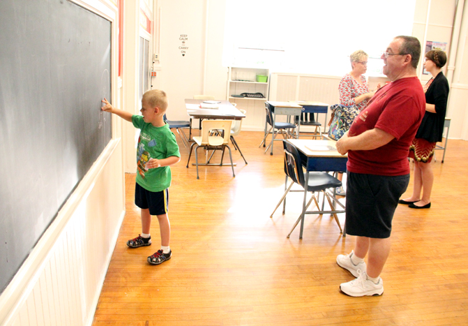 Tyler Pliska enjoys the classroom during the open house at the NHS school, as his parents learn more about it. (Sarah Webb)