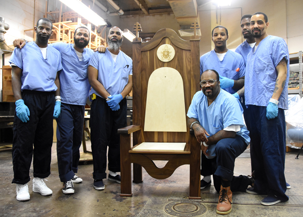 Inmates of Currran-Fromhold proudly stand by the chair as it will look when Pope Francis visits them Sept. 27.