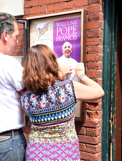 Staffers put up placards touting the papal visit, which hundreds of businesses in center city Philadelphia will soon receive, outside the Jack's Firehouse restaurant in Fairmount on Wednesday, Aug. 26.