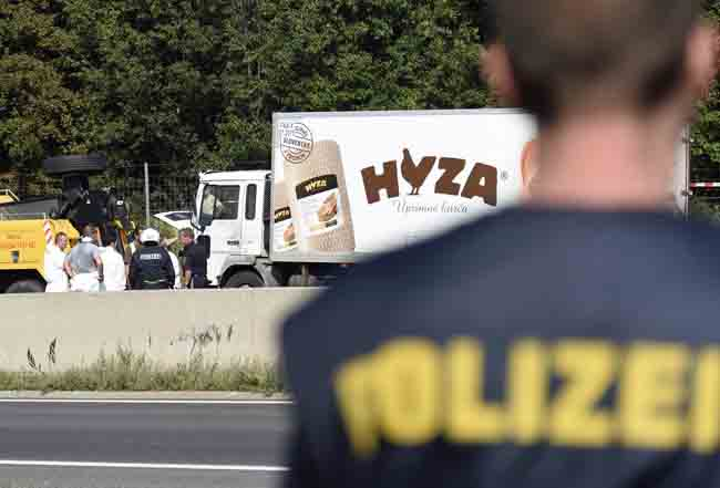 Forensic experts investigate a truck in which refugees were found dead on a freeway between Parndorf and Neusiedl, Austria, Aug. 27. (CNS photo/Herbert P. Oczeret)