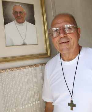 Salesian Brother Sal Sammarco poses next to a portrait of Pope Francis at a workshop in Port Chester, N.Y., Aug. 6. Brother Sammarco is overseeing a team of Latino day laborers who are constructing a chair that the pope will use when he celebrates Mass at Madison Square Garden Sept. 25 in New York City. (CNS photo/Gregory A. Shemitz)
