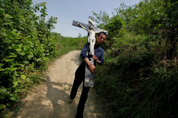 In this 2013 file photo, a Chinese Catholic carries a crucifix during a pilgrimage in the Shaanxi province of China. Hong Kong Cardinal John Tong Hon has asked Communist Party chiefs in Beijing to order a halt to an ongoing cross-removal campaign from churches in Zhejiang province. (CNS photo/Wu Hong, EPA)