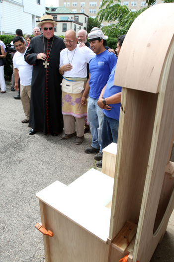 Cardinal Timothy M. Dolan of New York and Salesian Brother Sal Sammarco look at a chair Aug. 6 that Brother Sammarco and a team of Latino day laborers are constructing for Pope Francis in Port Chester, N.Y. (CNS photo/Gregory A. Shemitz)