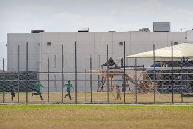 Children play in a double-fenced playground area in 2009 outside the T. Don Hutto Family Residential Facility in Taylor, Texas. The Catholic Legal Immigration Network and the Sisters of Mercy of the Americas decried the Obama administration's effort to have a judge set aside her orders for the release of families being held in immigration detention centers. (CNS photo/Bahram Mark Sobhani)
