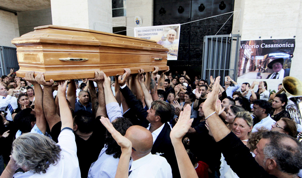 People carry the casket of Vittorio Casamonica into St. John Bosco Church in Rome for his Aug. 20 funeral Mass. Television programs, coffee bars, Italian Twitter accounts and the corridors of political power were abuzz Aug. 20-21 with news and commentary about the extravagance surrounding the funeral of the reputed boss of an organized crime ring in Rome. (CNS photo/Reuters)