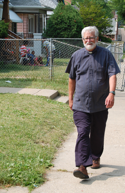 Father Bob Stiefvater, newly appointed pastor of All Saints Parish in Milwaukee, strolls through a neighborhood around the church on the city's north side July 10. He takes a daily walk in an effort to get to know the neighborhood and to let neighbors know of the church's presence. (CNS photo/Ricardo Torres, Catholic Herald)