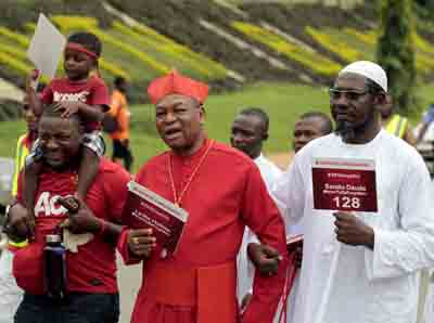Cardinal John Olorunfemi Onaiyekan of Abuja and Sheik Nura Khalid (right), chief imam of Apo Legislators Quarters Jumu'at Mosque, join #BringBackOurGirls campaigners in Abuja, Aug. 27. (CNS photo/Afolabi Sotunde, Reuters)