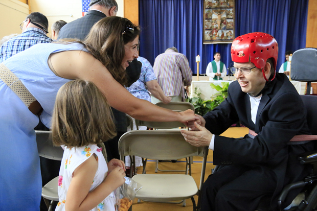 A Don Guanella resident, right, exchanges the sign of peace with a participant in the July 26 Mass at the Cardinal Krol Center in Springfield. It was the final event at the archdiocesan facility for 120 intellectually disabled men before they move into small, cottage-style housing in the fall. (Sarah Webb)