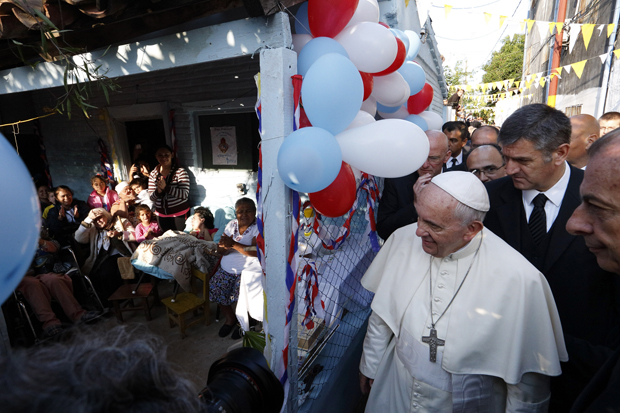 Pope Francis arrives to meet people gathered at a house as he visits Banado Norte, a poor neighborhood in Asuncion, Paraguay, July 12. (CNS photo/Paul Haring)