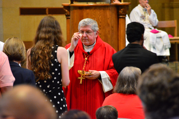 Cardinal Thomas Collins of Toronto offers Communion to a conference participant Aug. 10 at the Inn at St. John's in Plymouth, Mich., during the opening Mass of a three-day conference exploring the Catholic Church's ministry to those living with same-sex attraction. The international conference featured more than 30 speakers and was co-sponsored by Courage and the Archdiocese of Detroit. (CNS photo/Mike Stechschulte, The Michigan Catholic)
