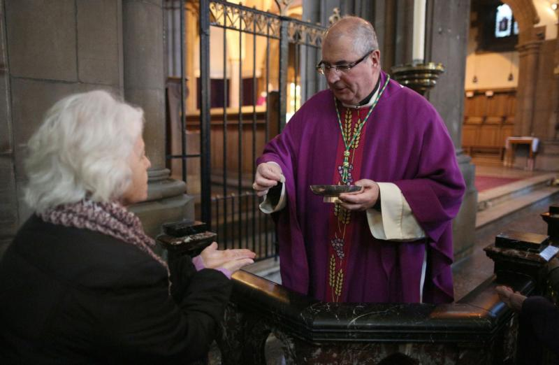 "Archbishop Philip Tartaglia of Glasgow, Scotland, serves Communion during Mass in 2013. Archbishop Tartaglia, president of the Scottish bishops' conference, offered a ""profound apology"" to victims of child abuse following a national review of church safeguarding procedures. (CNS photo/David Moir, Reuters)"