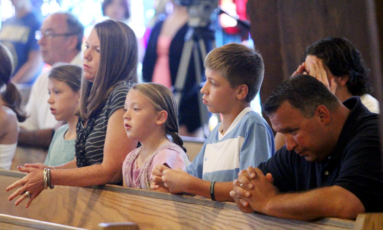 Riley, Bernadette, RIley, Matthew, Richard Bowes pray during mass