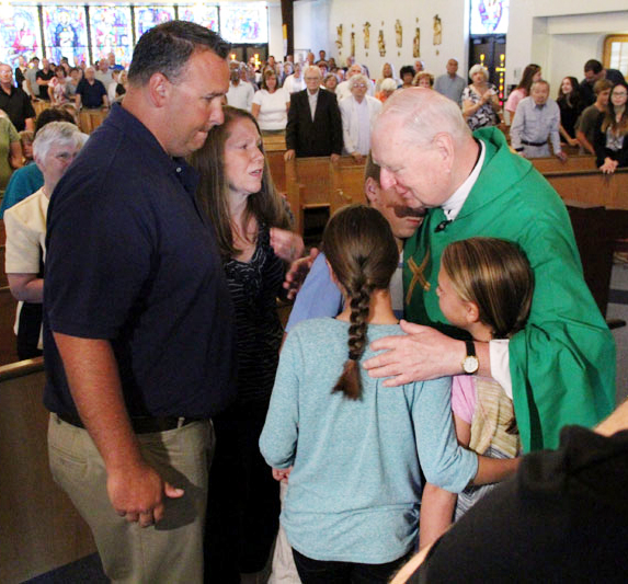 Msgr. Joseph Garvin embraces the Bowes family.