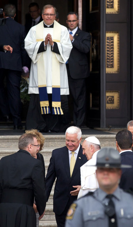 Father Dennis Gil, rector of The Cathedral Basillica of SS Peter and Paul, looks on as Pope Francis is greeted by Tom Corbett, former Pennsylvania governor. Photo by Bradley Digital.