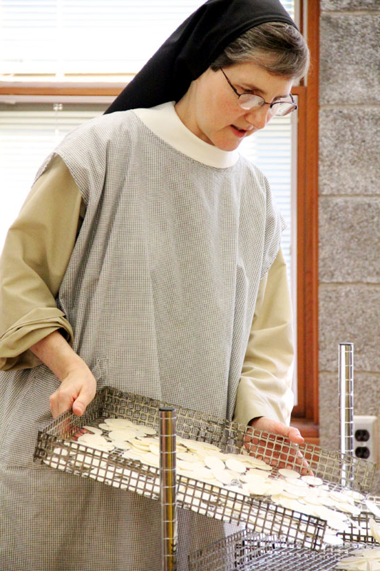 Sr Anne Bartol merges trays of freshly made hosts.