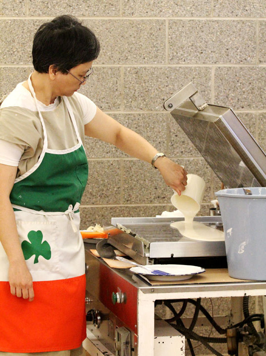 Postulate Maria Sison pours the batter.