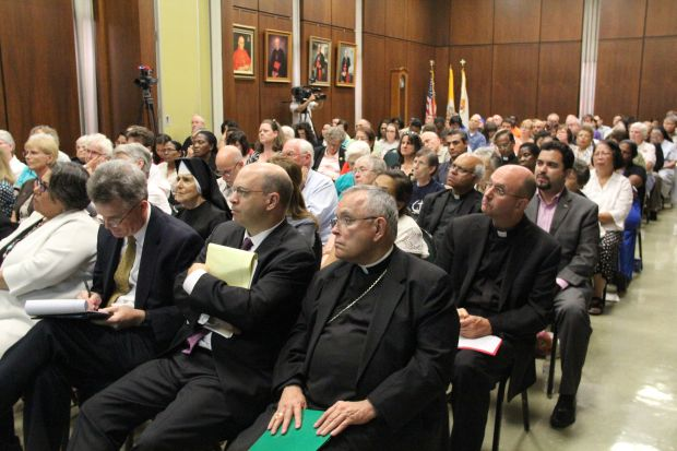 Archbishop Charles Chaput, who delivered the keynote talk at the immigration conference Sept. 1 at the Archdiocesean Pastoral Center in Philadelphia, listens to a speaker along with the audience. (Sarah Webb)