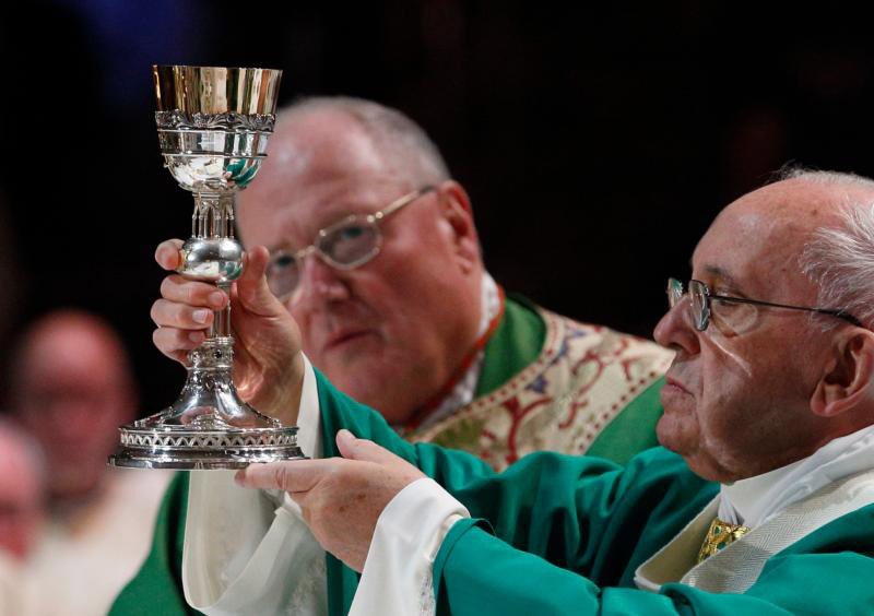 Pope Francis raises the chalice of the Eucharist as he celebrates Mass at Madison Square Garden in New York Sept. 25. Also pictured is Cardinal Timothy M. Dolan of New York.(CNS photo/Paul Haring) See POPE-NY-MASS Sept. 25, 2015.