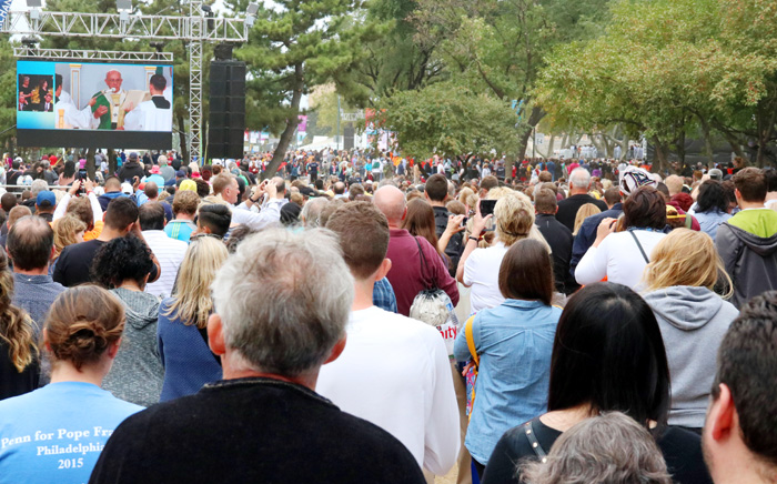 Crowds gather around one of the many monitors set up so all in attendence can see and hear Pope Francis as he celebrates Mass. Photo by Bob Kelly.