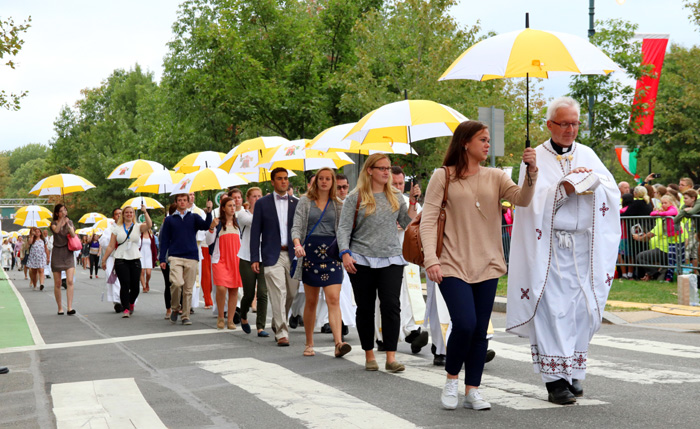 Priests are escorted down several blocks of Benjamin Franklin Parkway with umbrells to protect the Eucharist to distribut Holy Communion to hundreds of thousands. Photo by Bob Kelly.