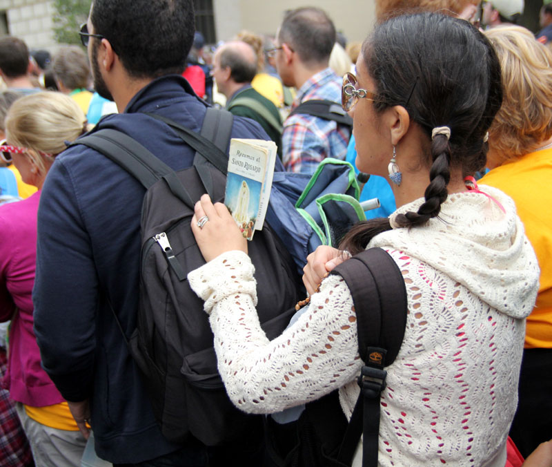 While waiting in line a woman prays the rosary. Photo by Sarah Webb