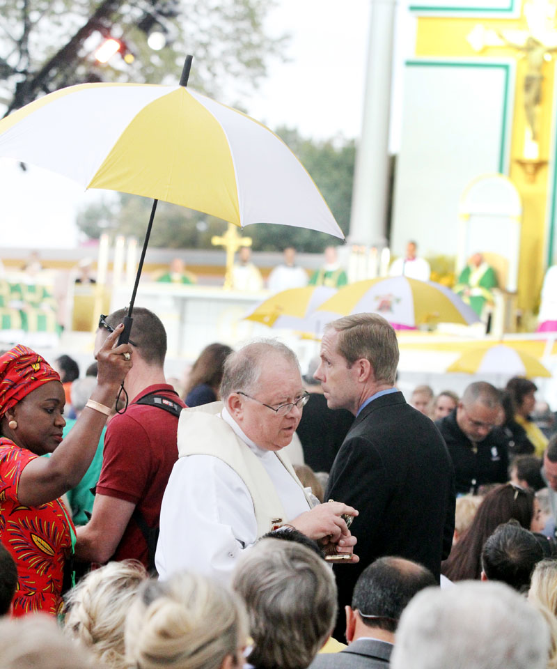 Priest are escorted by volunteers holding umbrellas over them and the Eucharist as they distribute Holy Communion. Photo by Sarah Webb