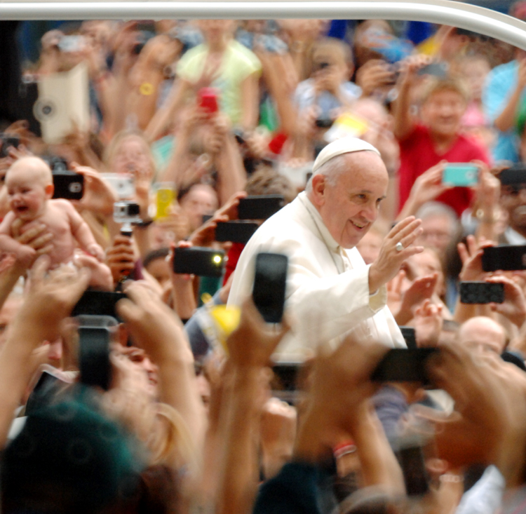 As the Pope Mobile drove down Benjamin Franklin Parkway people extended their babies in to the air in hopes the pontif would kiss they child. Photo by D'Mont Reese.