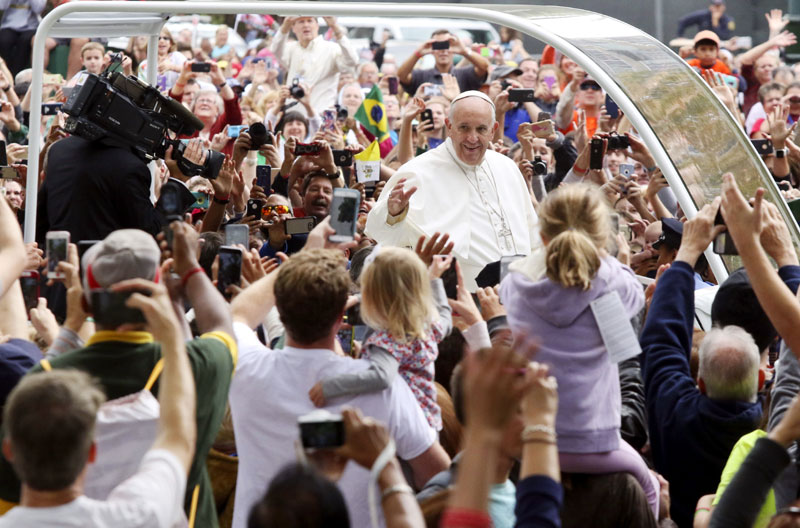 Pope Francis waves to the crowds in Philadelphia lining the Benjamin Franklin Parkway Sept. 27. (Photo by Kevin Cook)