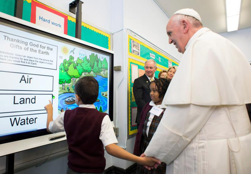 A student shows Pope Francis a lesson on the environment during his visit to Our Lady Queen of Angels School in the East Harlem area of New York Sept. 25. (CNS photo) See POPE-NY-IMMIGRANTS Sept. 25, 2015.
