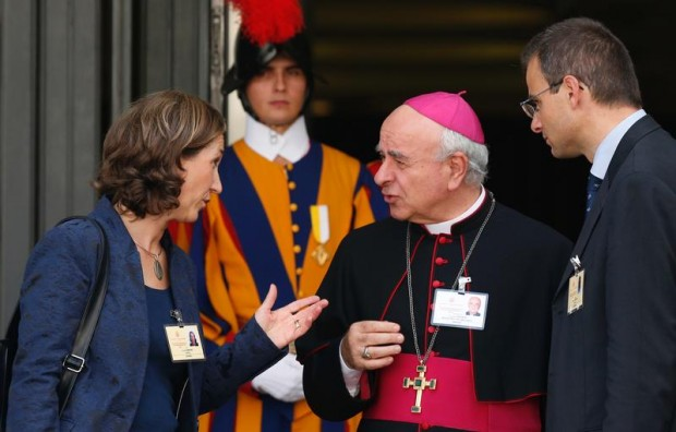 Archbishop Vincenzo Paglia, president of the Pontifical Council for the Family, talks with Xristilla and Olivier Roussy, auditors from France, as they leave the morning session of the extraordinary Synod of Bishops on the family at the Vatican Oct. 7. (CNS photo/Paul Haring)