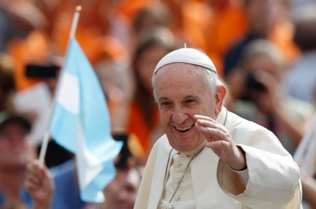 A pilgrim waves Argentina's flag as Pope Francis arrives to lead his general audience in St. Peter's Square at the Vatican Sept. 2. (CNS photo/Paul Haring)