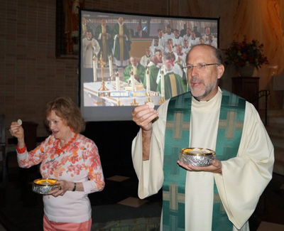 St. John Chrysostom parishioner Mary Anne Boylan and the Father Edward J. Hallinan, pastor, distribute Communion at the parish viewing of the papal Mass Sept. 27. (Photo by Debbie Cipolla)