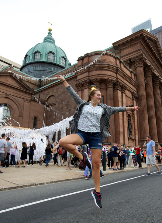 Seeing Pope Francis causes a girl to dance in the street outside The Cathedral Basillica of SS Peter and Paul. Photo by Bradley Digital.