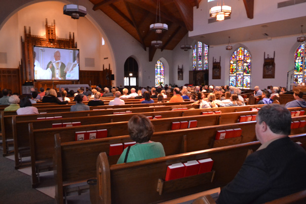 Parishioners of St. Monica Parish in Berwyn watch the Mass celebrated by Pope Francis on a big-screen TV in the church. (Elena Perri)