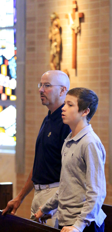 Tom and Tommy Carroll pray the Lord's Prayer