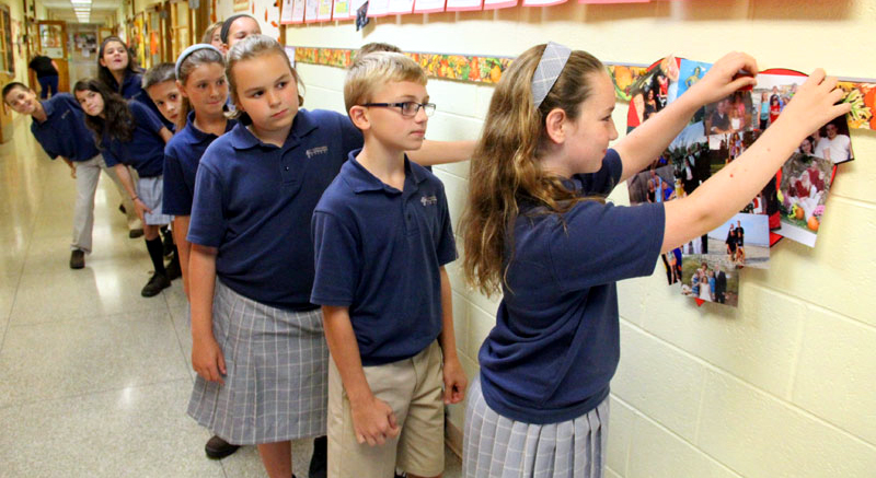 Fellow fifth graders was as Carolyn Connolly hangs the last picture to make their classes heart of families.