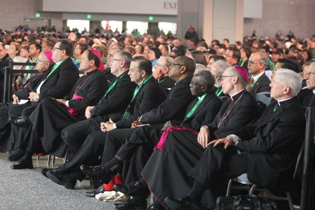 Bishops, including (from right) Toledo Bishop Daniel Thomas and Philadelphia Auxiliary Bishop Timothy Senior, and thousands of other attendees listen to Cardinal Tagle's address Sept. 24 at the World Meeting of Families in Philadelphia. (Sarah Webb)