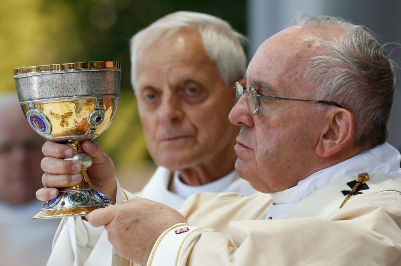 Pope Francis raises a chalice as he celebrates Mass outside the Basilica of the National Shrine of the Immaculate Conception Sept. 23 in Washington. (CNS photo/Paul Haring) See POPE-SERRA-MASS Sept. 23, 2015.