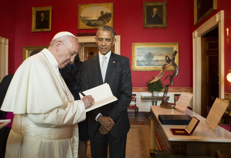 U.S. President Barack Obama looks on as Pope Francis signs a copy of an encyclical at the White House Sept. 23 in Washington. (CNS photo/L'Osservatore Romano handout via Reuters) See POPE-WHITE-HOUSE Sept. 23, 2015.