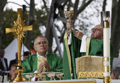 Pope Francis raises the chalice as he celebrates the closing Mass of the World Meeting of Families on Benjamin Franklin Parkway in Philadelphia Sept. 27. With him at the altar is Philadelphia Archbishop Charles J. Chaput. (CNS photo/Paul Haring)