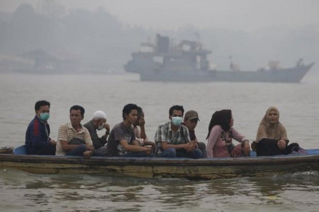 People cross the Batanghari River in Jambi, Indonesia, Sept. 14, while breathing unhealthy air caused by slash-and-burn deforestation. (CNS photo/Beawiharta, Reuters)
