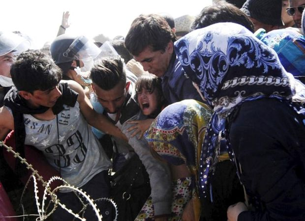 A young girl screams as migrants rush to cross into Macedonia at the Macedonian-Greek border Sept. 2. Catholic aid agencies have urged Europeans not to turn against migrants seeking refuge from Syria and other countries, in what media reports describe as the continent's greatest refugee movement since World War II. (CNS/Ognen Teofilovski, Reuters)