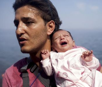 A Syrian refugee from Aleppo holds his 1-month-old daughter moments after arriving on a boat on the Greek island of Lesbos Sept. 3. (CNS/Dimitris Michalakis, Reuters)