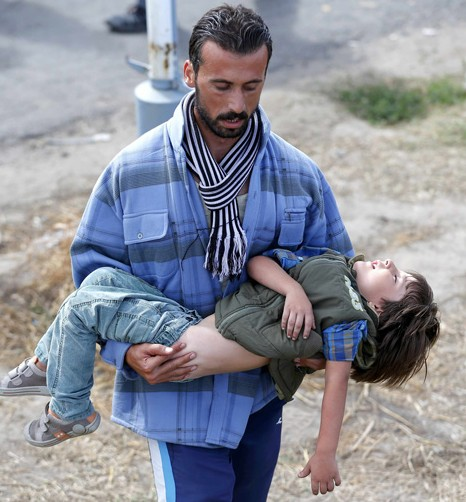 A migrant seeks medical attention for a child suffering with heatstroke in the village of Roszke, Hungary, Sept. 7. (CNS photo/Laszlo Balogh, Reuters)