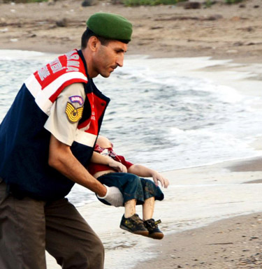 A member of the Turkish military carries a young migrant Sept. 2, who drowned in a failed attempt to sail to the Greek island of Kos, in the coastal town of Bodrum, Turkey. A Turkish media report says at least 11 migrants have died and five others are missing after boats carrying them to the Greek island of Kos capsized. (CNS photo/Reuters)